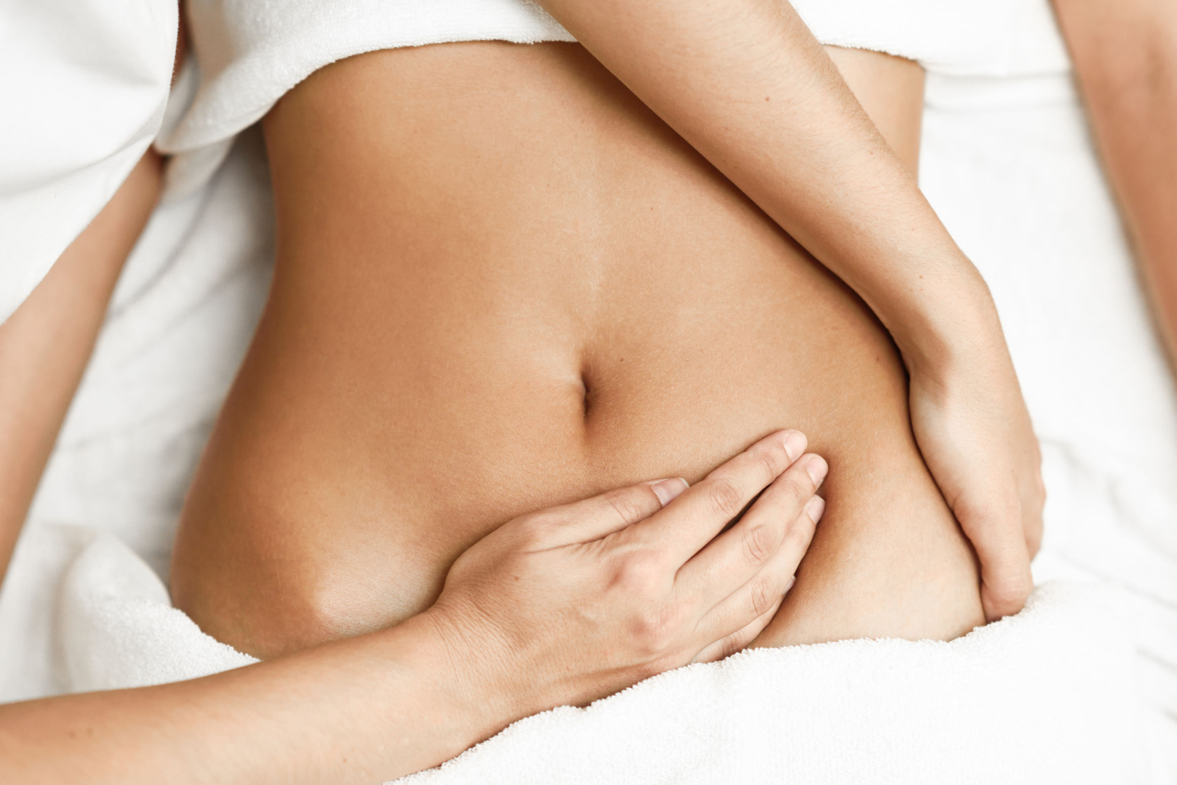 Hands treating female abdomen.Therapist applying pressure on belly.